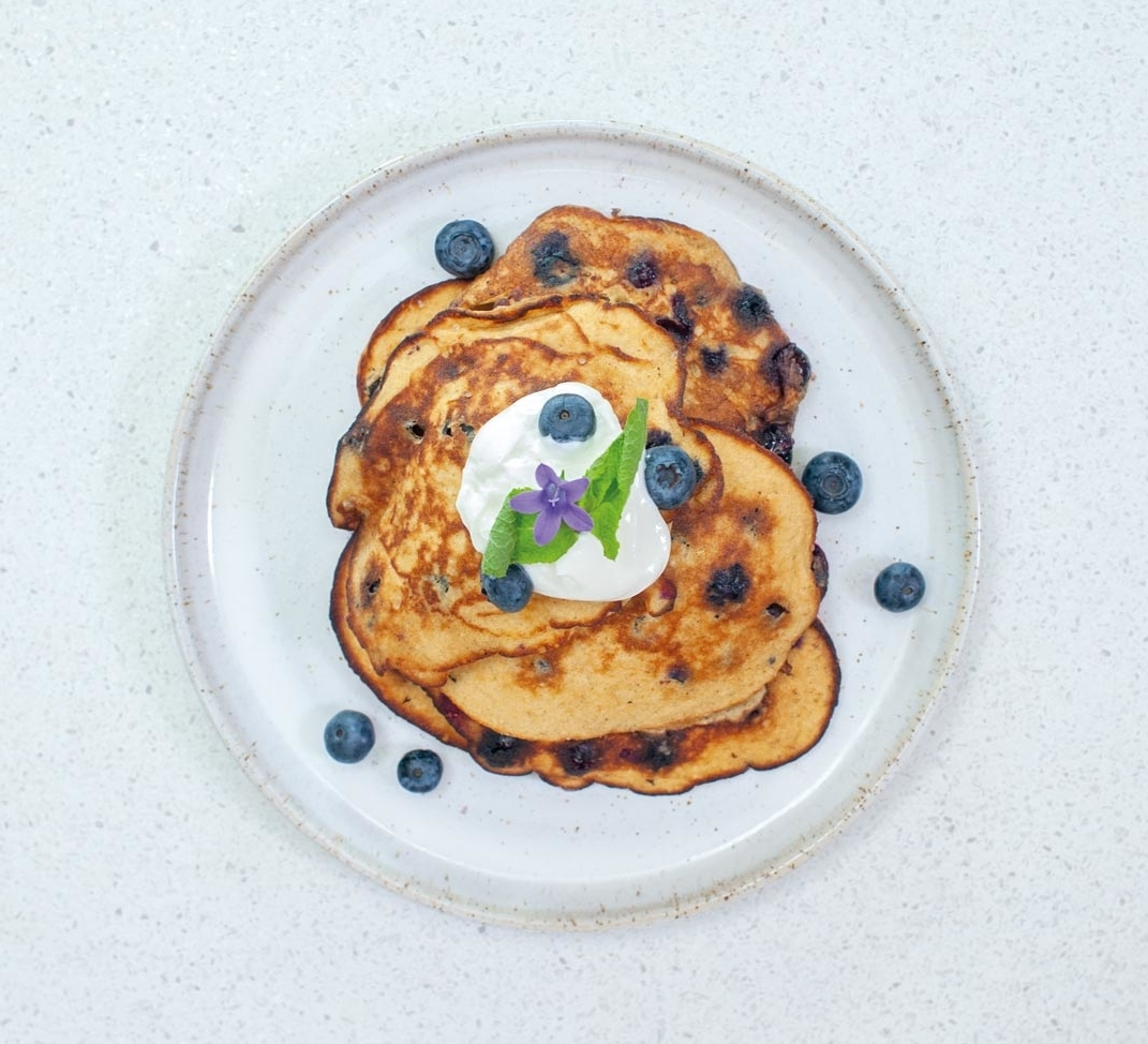 Blueberry oatmeal pancakes with a spoonful of natural yoghurt on top.