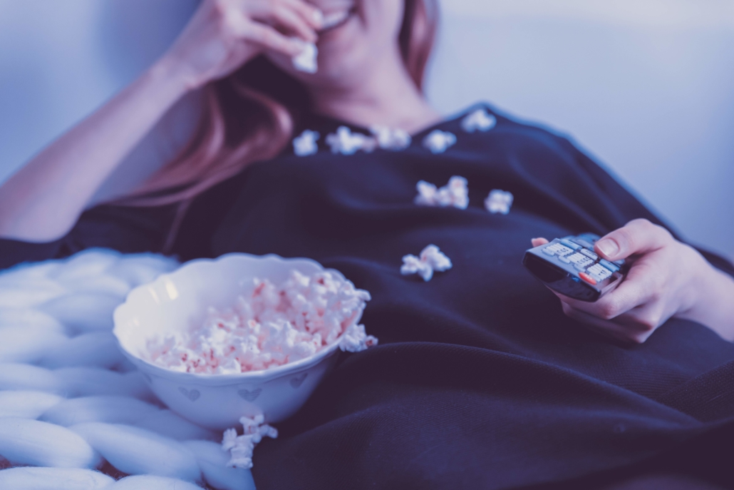 Woman eating popcorn in front of the tv.