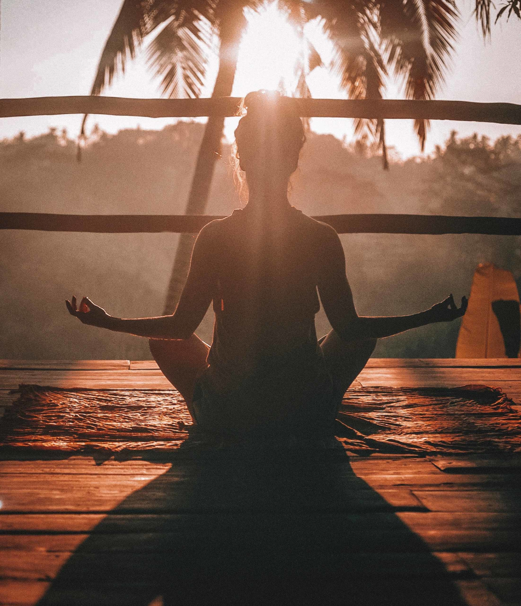 A person meditating during sunrise.